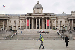 © Licensed to London News Pictures. <br /> London, UK. 24/03/2021. Members of the public are seen walking through Trafalgar Square, central London one year after the first coronavirus lockdown was announced. <br /> Photo credit: Marcin Nowak/LNP
