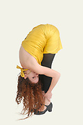 Balance concept red haired female model stretching out while maintaining balance on white background