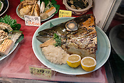 Fish head meal sample in restaurant window. Kabukicho entertainment and neon red-light district in Shinjuku ward, in Tokyo, Japan. Kabukicho was named from late-1940s plans to build a kabuki theater which never happened.