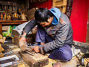 15 MARCH 2017 - BUNGAMATI, NEPAL:  A woodcarver in Bungamati works on a piece. Bungamati, a community of wood carvers and artisans, used to be a stop on the tourist trail of the Kathmandu valley but since the 2015 earthquake few tourists visit the community. Recovery seems to have barely begun nearly two years after the earthquake of 25 April 2015 that devastated Nepal. In some villages in the Kathmandu valley workers are working by hand to remove ruble and dig out destroyed buildings. About 9,000 people were killed and another 22,000 injured by the earthquake. The epicenter of the earthquake was east of the Gorka district.            PHOTO BY JACK KURTZ