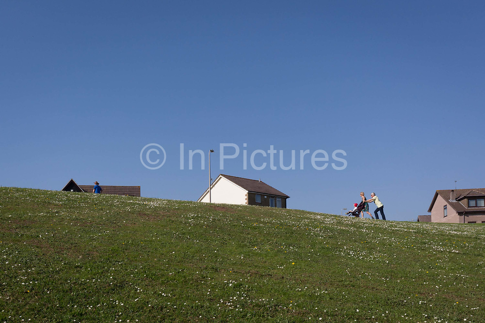 A local family walk uphill towards the houses of a nineteen-eighties, middle-class housing estate on 21st April 2019, in Nailsea, North Somerset, England.