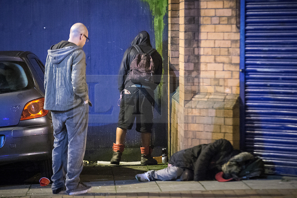 © Licensed to London News Pictures . 01/11/2015 . Manchester , UK . A man urinates against a wooden hoarding close to another man who is sleeping on the pavement , opposite Deansgate Locks . Halloween revellers , wearing make up and costumes , out and about in Manchester City Centre . Photo credit : Joel Goodman/LNP