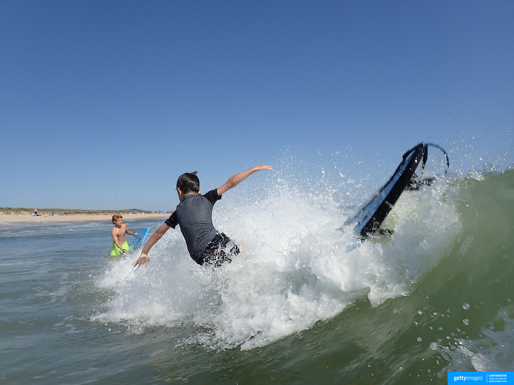 A young boy attempts to surf in the height of summer on Cisco Beach, Nantucket, Nantucket Island, Massachusetts, USA. Photo Tim Clayton