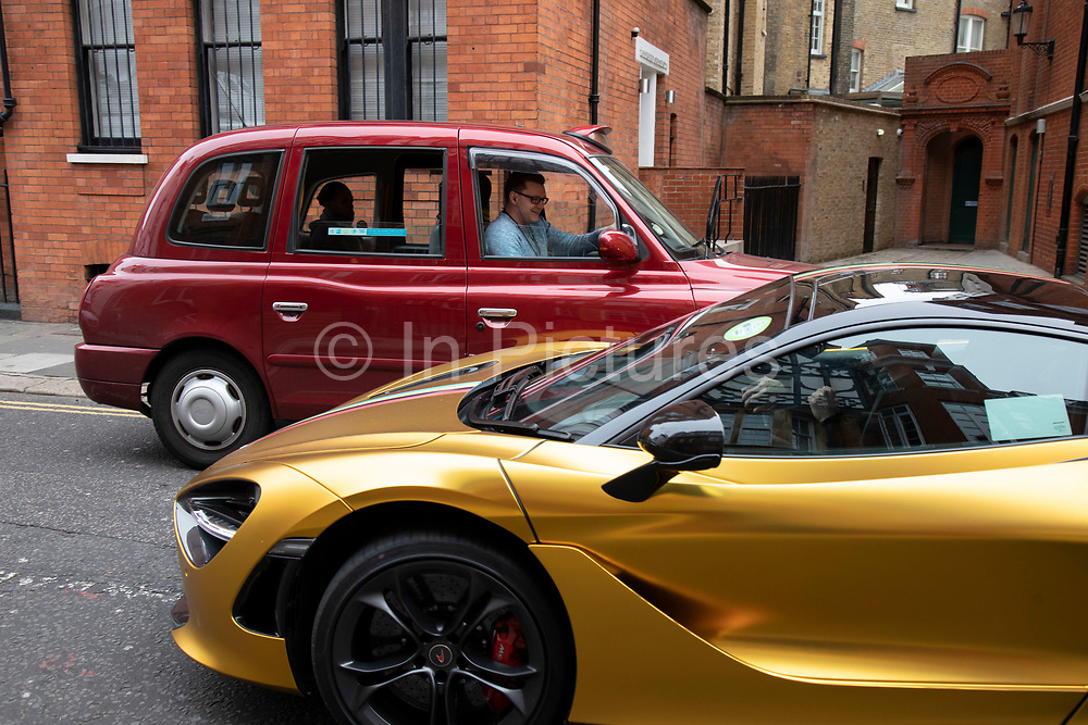 Gold McLaren sports car passes a mere Taxi in the wealthy area of Knightbridge in London, United Kingdom. This is an area where the rich in their supercars parade them around driving with little more reason than showing off their exclisive cars.