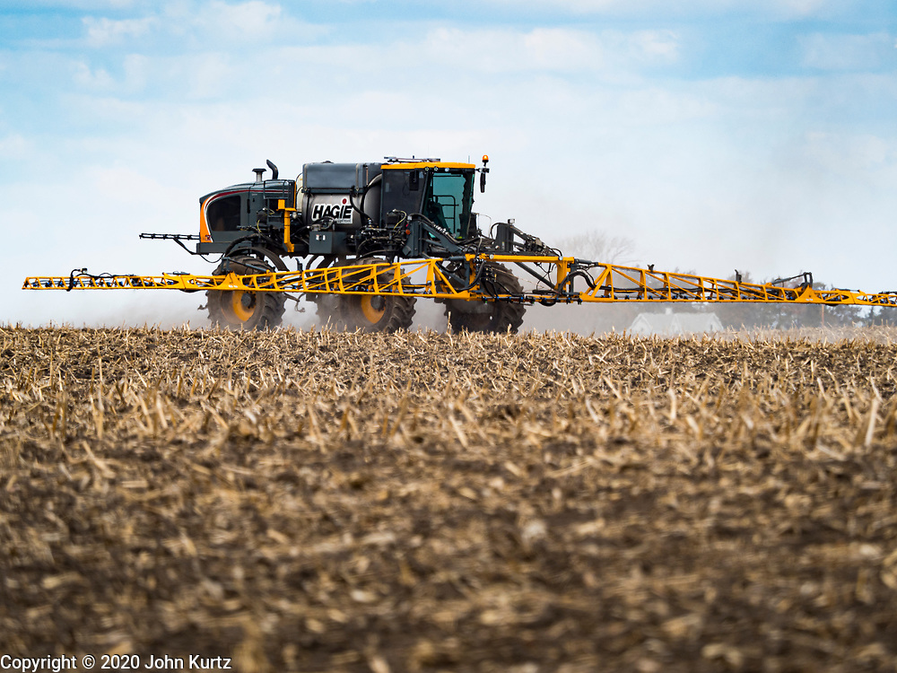 """20 APRIL 2020 - BOUTON, IOWA: A spreader applies fertilizer to a field near Bouton. Iowa farmers are prepping their fields for the 2020 season. The relatively mild winter and dry spring has allowed farmers to get into their fields 1 - 2 weeks earlier than last year. Farmers and agricultural workers are considered """"essential"""" workers in Iowa and not subjected to the coronavirus restrictions nonessential workers are. Farmers usually work by themselves, and social distancing guidelines have not impacted them as much as it has workers in Iowa's cities.   PHOTO BY JACK KURTZ"""