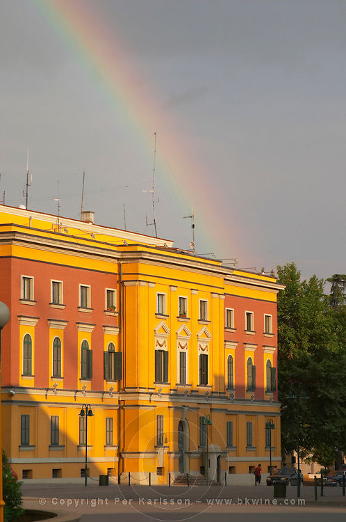 National administrative buildings in bright yellow and red in classic architecture style around the square. A rainbow in the sky. The Tirana Main Central Square, Skanderbeg Skanderburg Square. National Tourist Organisation. Tirana capital. Albania, Balkan, Europe.