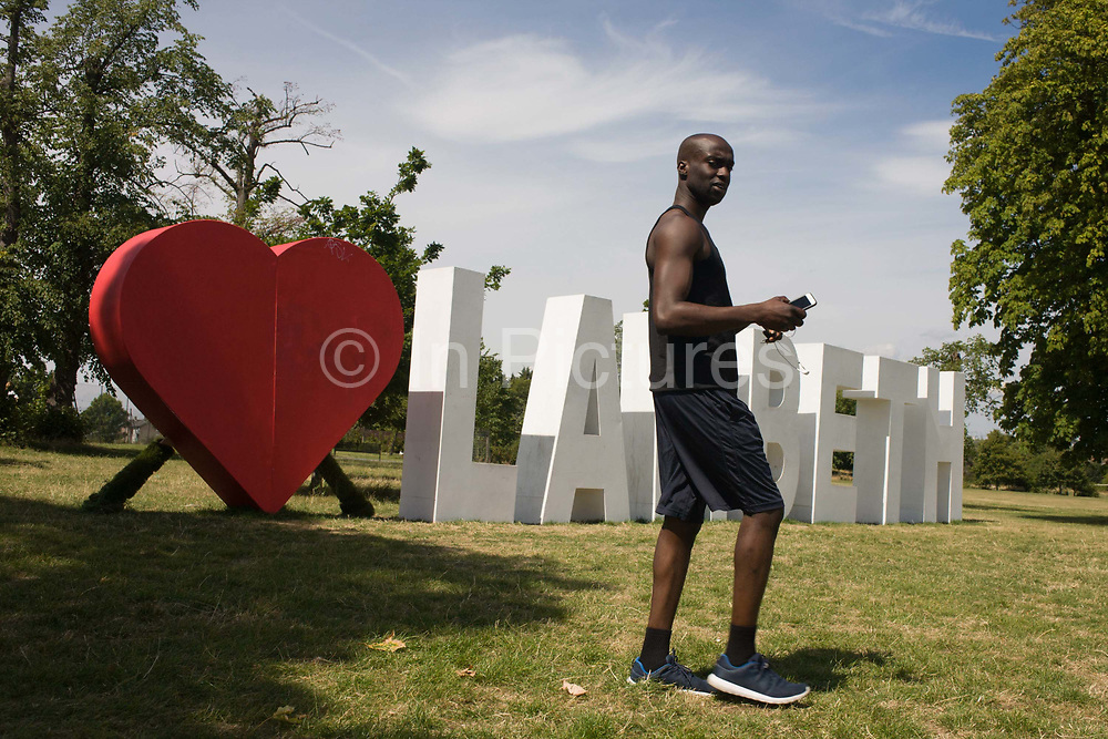 Tall black man with giant letters across the grass in Brockwell Park in Herne Hill, SE24., spelling Lambeth, the largest in area, of London boroughs. The letters are a remnant of the Lambeth Country Show, an annual iner-city weekend festival featuring local businesses and entertainment, it celebrates the successes of Lambeth's achivevements for its population of approximately 303,000.