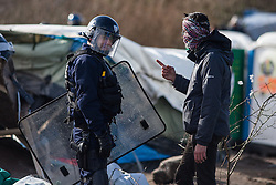 Licensed to London News Pictures. 03/03/2016. Calais, France. A refugee remonstrates with a riot policeman as makeshift shelters are torn down. French authorities are clearing the southern half of the Calais 'Jungle' camp, which charities estimate to contain 3,500 people. Photo credit : Rob Pinney/LNP