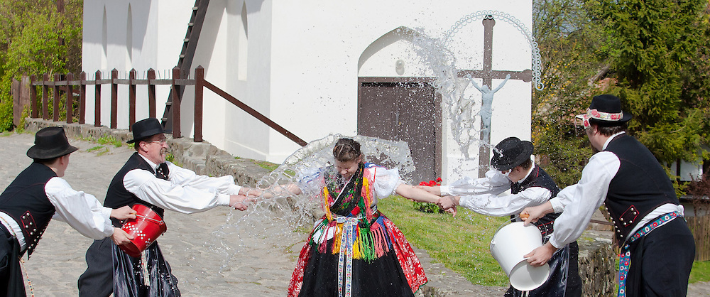 """Men hold onto a woman as they throw water at her, as part of traditional Easter celebrations, during a media presentation in Holloko, 100 km (62 miles) east of Budapest, Hungary on April 14, 2011..Locals from the World Heritage village of Holloko, celebrate Easter with the traditional """"watering of the girls"""", a Hungarian tribal fertility ritual rooted in the area's pre-Christian past. ATTILA VOLGYI"""