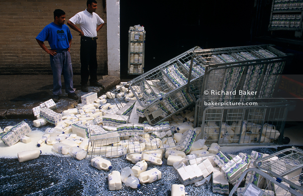 Two dairy employees stand with hands on hips over crates of spilled milk, tipped over into the gutter of a London street.