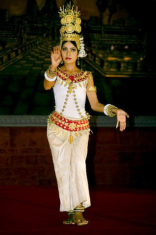 Full length frontal portrait of a costumed apsara dancer in performance.