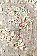 detail of ornamental lace embroidery with a red thread