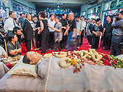 12 OCTOBER 2104 - BANG BUA THONG, NONTHABURI, THAILAND: People file past the body of Apiwan Wiriyachai, at his funeral rites at Wat Bang Phai in Bang Bua Thong, a Bangkok suburb, Sunday. Apiwan was a prominent Red Shirt leader, member of the Pheu Thai Party of former Prime Minister Yingluck Shinawatra, and a member of the Thai parliament. The military government that deposed the elected government in May, 2014, charged Apiwan with Lese Majeste for allegedly insulting the Thai Monarchy. Rather than face the charges, Apiwan fled Thailand to the Philippines. He died of a lung infection in the Philippines on Oct. 6. The military government gave his family permission to bring him back to Thailand for the funeral. He will be cremated later in October. The first day of the funeral rites Sunday drew tens of thousands of Red Shirts and their supporters, in the first Red Shirt gathering since the coup.    PHOTO BY JACK KURTZ