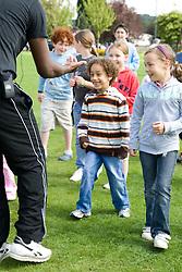 Dance teacher encouraging a group of children at a Parklife summer activities event,