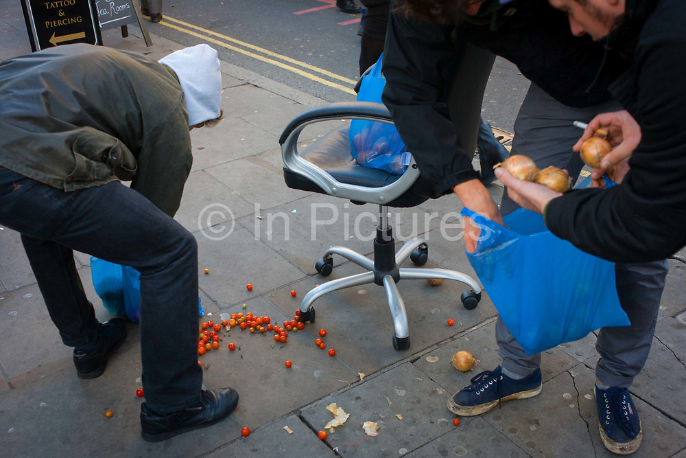 Shoppers in the street pick-up dropped tomatoes and onions. Gathering the spilled produce from the pavement, a man bends down and reaches for the valuable fruit and vegetables into blue polythene bags - helped by others who have stopped to help prevent them from rolling away into the gutter. The street is Brick Lane in the east end of London, an area for Bangladeshi community's businesses.