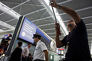 A General Electric advertisement above a cleaner and pilot near security departure gate at Heathrow Airport's Terminal 5.