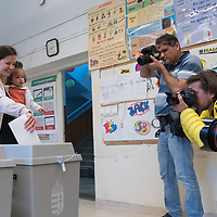 Photographers take pictures as family cast their vote during the European Parliamentary election in Budapest, Hungary on May 26, 2019. ATTILA VOLGYI