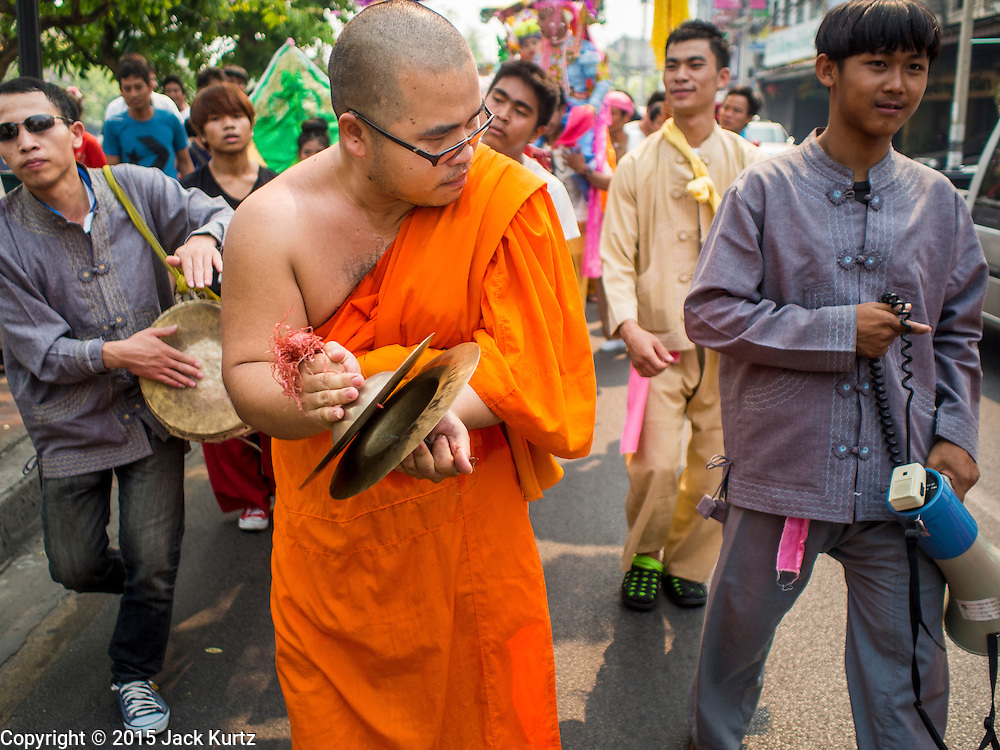 """05 APRIL 2015 - CHIANG MAI, CHIANG MAI, THAILAND: As Buddhist monk plays cymbals and leads a parade during the second day of the three day long Poi Song Long Festival in Chiang Mai. The Poi Sang Long Festival (also called Poy Sang Long) is an ordination ceremony for Tai (also and commonly called Shan, though they prefer Tai) boys in the Shan State of Myanmar (Burma) and in Shan communities in western Thailand. Most Tai boys go into the monastery as novice monks at some point between the ages of seven and fourteen. This year seven boys were ordained at the Poi Sang Long ceremony at Wat Pa Pao in Chiang Mai. Poy Song Long is Tai (Shan) for """"Festival of the Jewel (or Crystal) Sons.    PHOTO BY JACK KURTZ"""