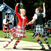 August 18, 2007 -- BRUNSWICK, Maine.   Chloe White,13, of St. Catherine's, Ont., left, and Allyson Naegeli, 15, of Francestown, NH dance a Strath Spey and Reel at The Maine Highland Games. The piper is Jay Conant of Hampton, NH. Both girls were award winners in their competition classes. Photo by Roger S. Duncan.