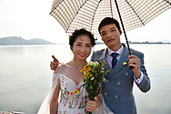 Wedding couple standing in front of the lake in East Lake Greenway park, Wuhan, Hubei, China