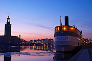 Wide panoramic Evening view at sunset over an ice covered Riddarfjarden water towards the west with Kungsholmen and Stadshuset the Town Hall reflected in the water a white ship moored at key at Riddarholmen. Iceflakes ice flakes Stockholm, Sweden, Sverige, Europe