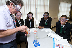 Secondary School teacher demonstrating a titration chemistry experiment to a group of students,
