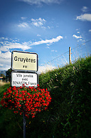Photo of a street sign in Gruyere, Switzerland decorated with red flowers