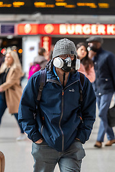 © Licensed to London News Pictures. 16/03/2020. London, UK. A London commuter on his way to work in an unusual mask at a quiet Victoria Station this morning as Government ministers warn that over 70s will face self-isolation for weeks as the Coronavirus disease pandemic continues . Photo credit: Alex Lentati/LNP