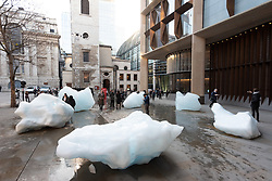 © Licensed to London News Pictures. 11/12/2018. London, UK. Commuters view the  Ice Watch display of blocks of melting glacier ice across two public sites in the centre of London to create a major artwork. Photo credit: Ray Tang/LNP