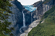 """Waterfalls plunge from Queulat Hanging Glacier, in Queulat National Park, Aysen Province, Chile, Andes mountains, Patagonia, South America. Queulat Hanging Glacier, the park's centerpiece, extends from the Queulat ice cap, which borders the northernmost part of the Puyuhuapi Channel called Ventisquero Sound (actually a fjord, carved by glaciers). Sendero Ventisquero Colgante, the best trail in the park, reaches Mirador Ventisquero Colgante (Viewpoint of Queulat Hanging Glacier). Hike 4 miles or 6.6 km round trip with 1150 ft ft or 350 m cumulative gain. Cross a suspension bridge (where the limit of 4 people at a time can cause significant waits). Walk a rocky and rooty yet popular trail through dense forest. Go early in the morning to avoid crowds. The park is one of the rainiest places (3500 - 4000 mm) in Chilean Patagonia. Ventisquero (or """"snowdrift"""") is an archaic word for """"glacier"""" used by early South American explorers."""