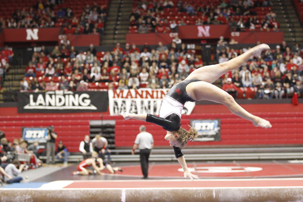 Danielle Breen competes on the beam while the wrestling team takes on Northwestern in the background at the Bob Devaney Sports Center in Lincoln, Neb., on Feb. 12, 2016. Photo by Aaron Babcock, Hail Varsity