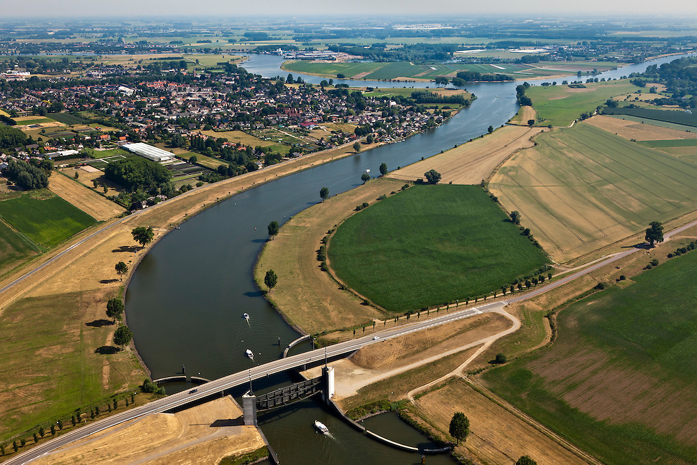 Nederland, Noord Brabant, Wijk en Aalburg, 08-07-2010. Heusdensch Kanaal met stormvloedkering, keersluis, Kromme Nolkering  (keersluis Kromme Nol). Het kanaal verbindt de Afgedamde Maas met de Bergsche Maas (onder). De kering beschermt de dijken langs het Heusdensch Kanaal en de Afgedamde Maas bij zeer hoge waterstanden..Heusdensch Channel with flood barrier, floodgate. The canal connects the two (old) branches over river Meuse..luchtfoto (toeslag), aerial photo (additional fee required).foto/photo Siebe Swart.
