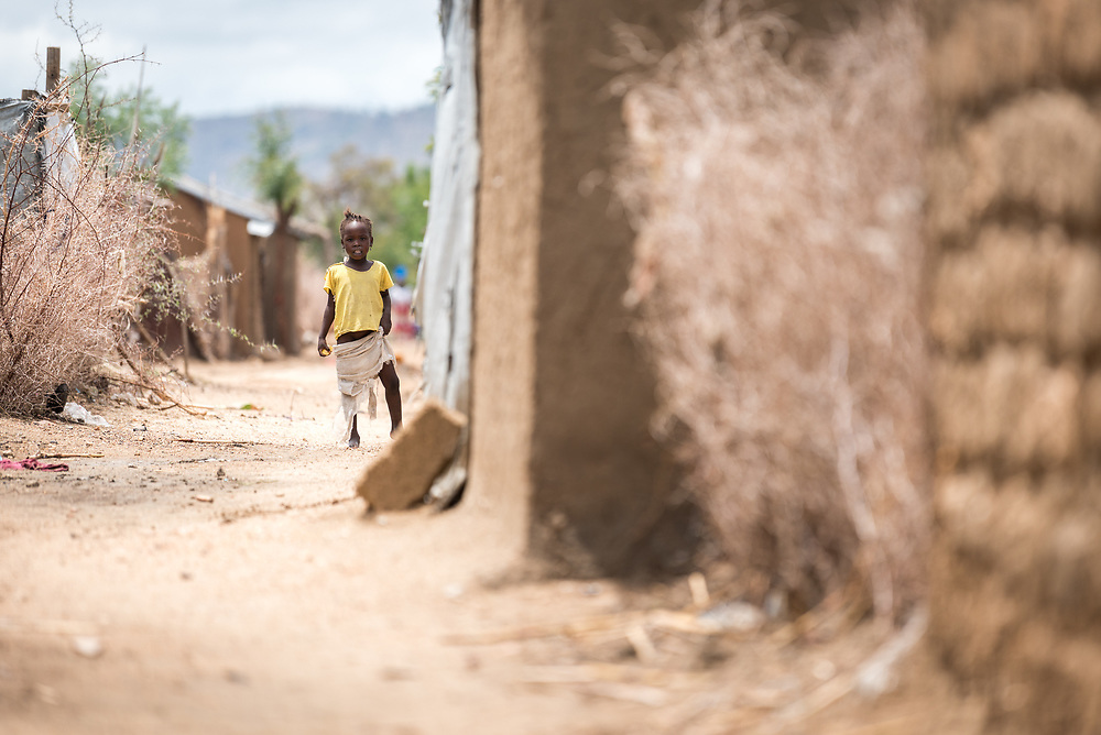 30 May 2019, Mokolo, Cameroon: A girl looks out from her home in the Minawao camp for Nigerian refugees. The Minawao camp for Nigerian refugees, located in the Far North region of Cameroon, hosts some 58,000 refugees from North East Nigeria. The refugees are supported by the Lutheran World Federation, together with a range of partners.