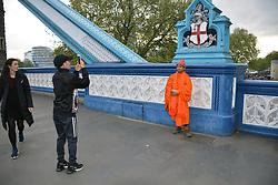 Buddhist monk having his picture taken on Tower Bridge, London UK April 2019
