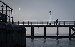 © Licensed to London News Pictures. 30/12/2016. Portsmouth, UK.  A fisherman watches as the sun glows through the fog. People on the South Coast have woken up to foggy weather this morning, 30th December 2016. Photo credit: Rob Arnold/LNP