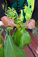Julie Bicoy preparing a ho'okupu, a gift of food wrapped in a Ti leaf, for entrance into the Halawa Valley, Molokai, Hawaii, USA