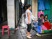 30 MAY 2013 - BANGKOK, THAILAND: A woman and her son come out of an alley in Bobae Market in Bangkok. Bobae Market is a 30 year old famous for fashion wholesale and is now very popular with exporters from around the world. Bobae Tower is next to the market and  advertises itself as having 1,300 stalls under one roof and claims to be the largest garment wholesale center in Thailand.     PHOTO BY JACK KURTZ