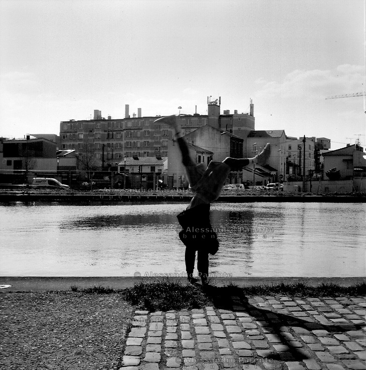 Aubervilliers, Seine Saint Denis. An artist from the Cirque du Soleil is making some exercise along the canal.