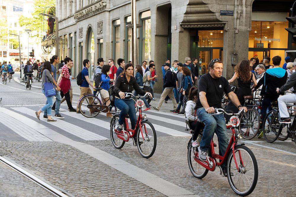 In Amsterdam rijdt een gezin op vakantie huurfietsen door de binnenstad.<br /> <br /> In Amsterdam a family on holiday are riding  rental bikes downtown.