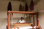 A Zapotec indigenous man uses a pedal hand loom to weave traditional carpets in Teotitlan de Valle, Mexico.