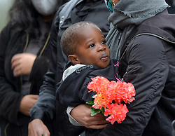 Pictured: Mercy's son Adriel at the vigil, holding a bunch of flowers.<br /> <br /> Friends and supporters held a vigil in Govan in memory of tragic asylum seeker Mercy Baguma, who was found dead next to her baby son on 22nd August at a flat in the city.<br /> <br /> © Dave Johnston / EEm