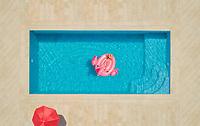 Aerial view of girl lying on inflatable flamingo in pool, Sumarti, in Croatia.