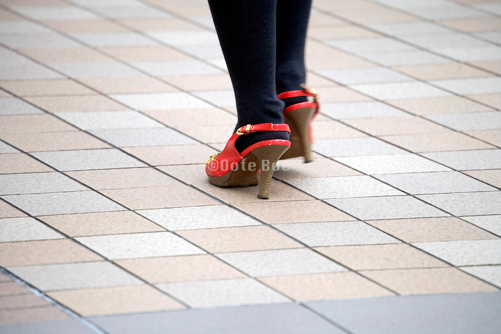 woman in red high heel shoes walking