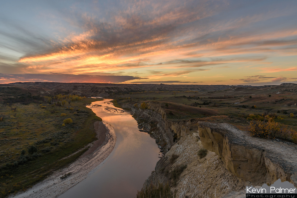 A vibrant sunset is reflected in the muddy waters of the Little Missouri River. This river flows over 500 miles on it's way to the Big Missouri. Echoing across the wilderness was the sound of bugling elk, and stampeding bison. The Wind Canyon overlook is one of the most scenic views in Theodore Roosevelt National Park. The 26th president started a cattle ranch here in 1885. Even though the harsh North Dakota winter drove him out a few years later, it was his time here that inspired him to establish many national parks, forests, and wildlife refuges.
