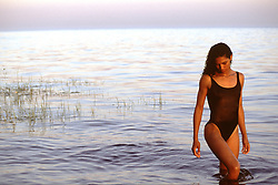 American American woman in a swimsuit standing in the bay at sunset