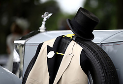 A top hat and waistcoat rests on a spare tyre on a car during day one of Royal Ascot at Ascot Racecourse.