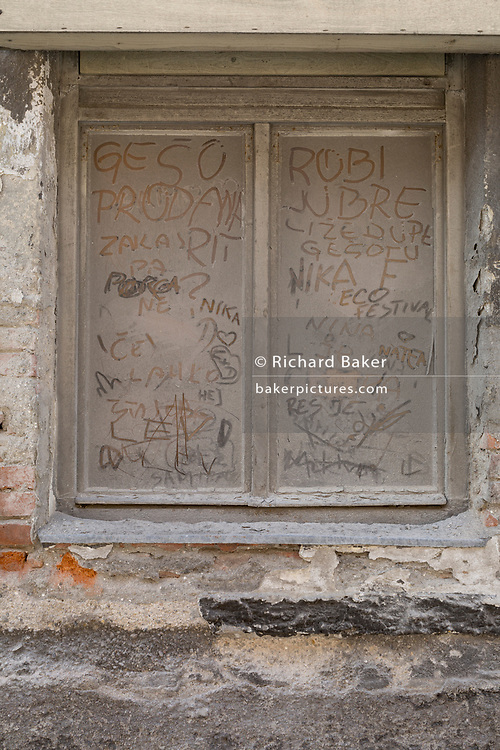 Dirty window with local names and messages written on the glass,  on 25th June 2018, in Skofja Loka, Slovenia.