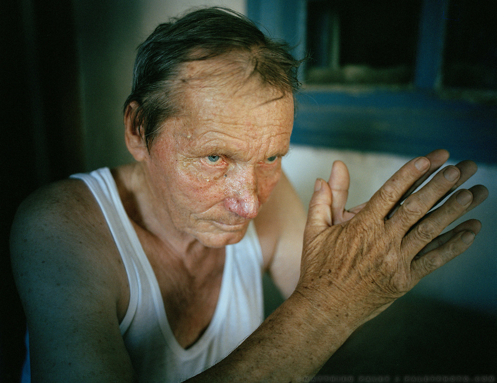 PIotr Ivanovich, born Moynaq, 75 yrs old, thinks of days when he was the captain of his boat, now beached in the desert near Moynaq. Eyes blue as the long gone sea!<br /> <br /> In Moynaq town, former fishing port on the Aral Sea, now 180km from shore. <br /> Since 1960's, The Aral Sea has been drained of 75% of its water, because of the diversion of upstream rivers that are used for cotton plantation. It use to be the 4th largest lake in the world. The resulting desertification is accelerating dramatically global warming. High salinity means no more fish. Anthrax and rabbies test were also done in a former island in the sea that is now linked to the shore.... <br /> Uzbekistan.