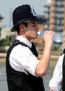 © Licensed to London News Pictures. 25/07/2012. London, UK .  A policeman drinks water as temperatures reach 30 degrees at Greenwhich Pier in London today 25 July 2012. Photo credit : Stephen Simpson/LNP