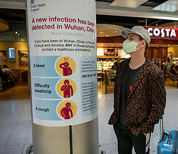 © Licensed to London News Pictures. 24/01/2020. London, UK. Passengers arrive with protective masks on as signs have been installed around Heathrow Terminal 4, warning passengers of the symptoms of the new Wuhan coronavirus outbreak. The coronavirus virus has infected more than 800 people across Asia in the past few weeks Photo credit: Alex Lentati/LNP